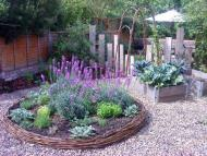 Family garden with circular willow bed and archway plus reclaimed wood for pathways and screening.