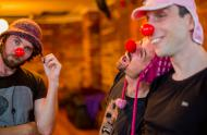 three men with red noses and silly hats looking clownish