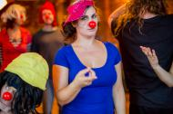 A woman in a blue top and a pink hat, with a red nose, pointing at the camera