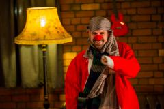 grinning man wearing a clown's red nose, a red coat and a scarf around his head, standing in front of a brick wall, beside a yellow standard lamp