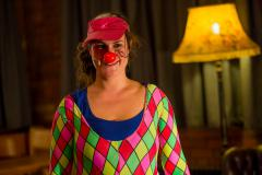 woman in a pink harlequin top, a pink sequinned visor and a red clown's nose, smiling