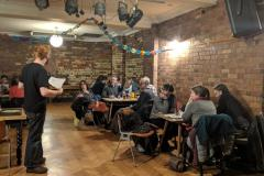 Quiz host reading questions to rapt quizzers