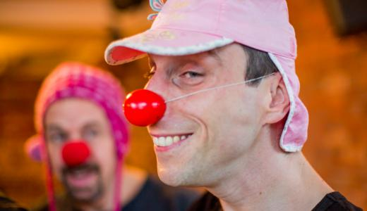 two men with red noses and silly hats looking clownish